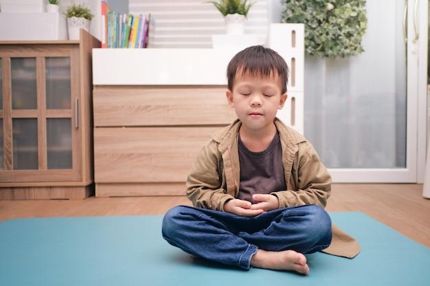 Aziatische jongen beoefent yoga en mediteert thuis