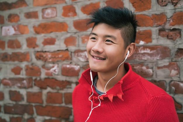Aziatische jongen die aan muziek met oortelefoons luistert.