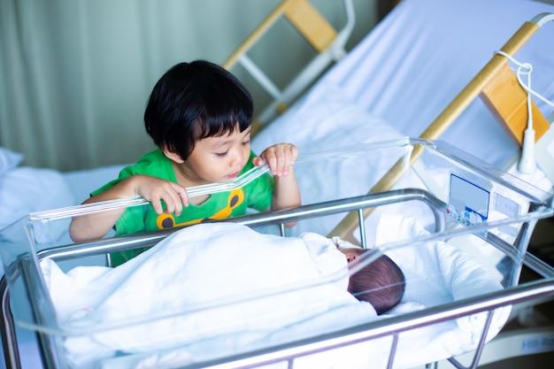 Aziatische jongen die aan zijn pasgeboren broer kijkt