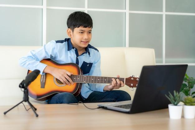 Aziatische jongen die akoestische gitaar online met vrienden speelt
