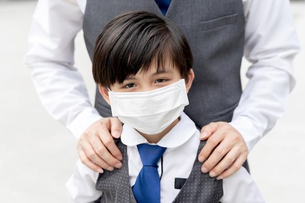 Aziatische jongen die beschermend gezichtsmasker draagt ter bescherming tijdens de uitbraak van quarantaine coronavirus covid 19