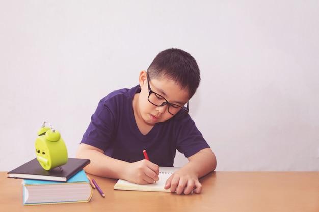 Aziatische jongen die een boek op lijst schrijft