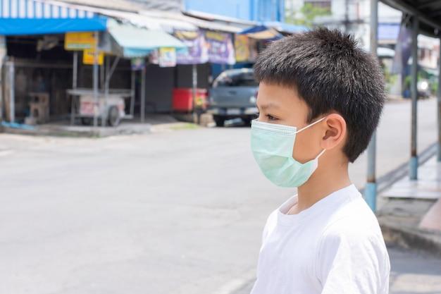 Aziatische jongen die een masker draagt dat zich op de straat in bangkok, thailand bevindt.
