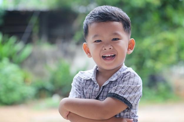 Aziatische jongen die gelukkig glimlacht en zich met zijn gekruiste handen bevindt.