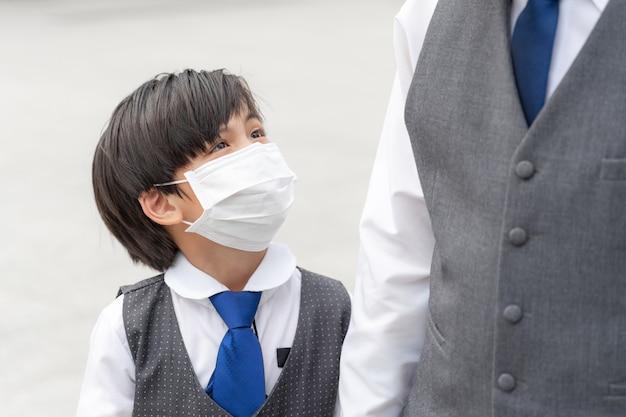 Aziatische jongen die gezichtsmasker draagt, verspreidt covid-19 coronavirus, aziatische familie die gezichtsmasker draagt voor bescherming