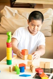 Aziatische jongen die houten blok speelt