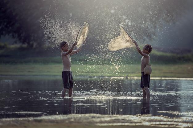 Aziatische jongen die in het meer vissen