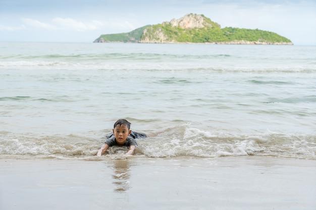 Aziatische jongen die in het overzees dichtbij het strand in ao manao, prachuap khiri khan, thailand genieten