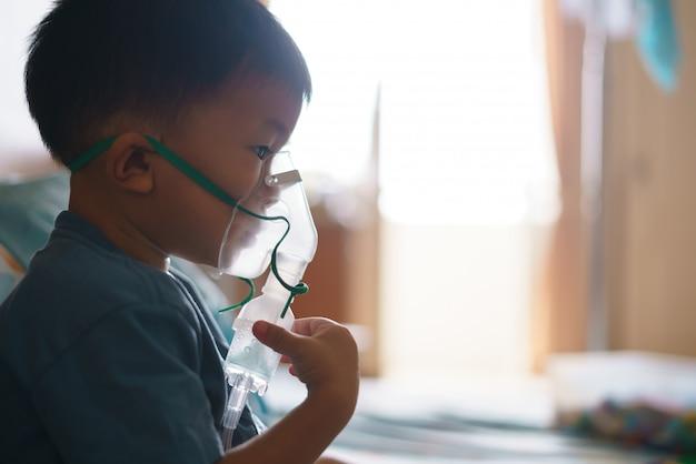 Aziatische jongen die inhaleertoestel gebruikt dat geneeskunde houdt ophouden met hoesten