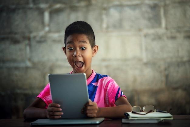 Aziatische jongen die laptop op de lijst gebruikt, komt terug naar school