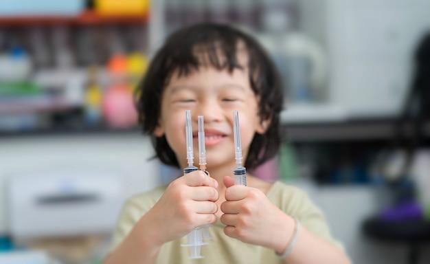 Aziatische jongen die met glimlachgezicht drie spuiten op hand op onduidelijk beeldachtergrond houdt