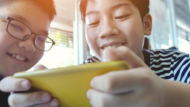 Aziatische jongen die mobiel spel op slimme telefoon samen speelt.