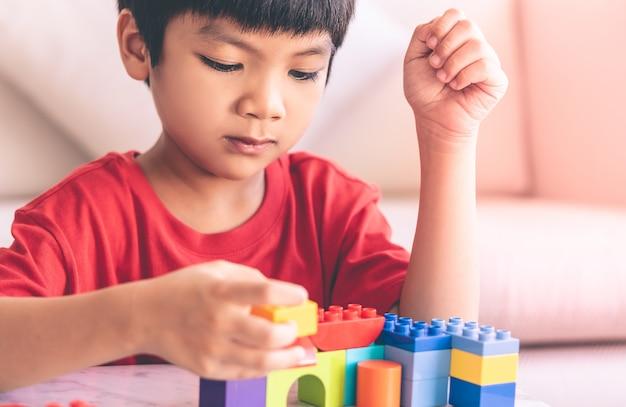 Aziatische jongen die stuk speelgoed blokken op een lijst stapelt