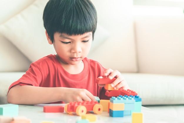 Aziatische jongen die stuk speelgoed blokken op een woonkamerlijst stapelt