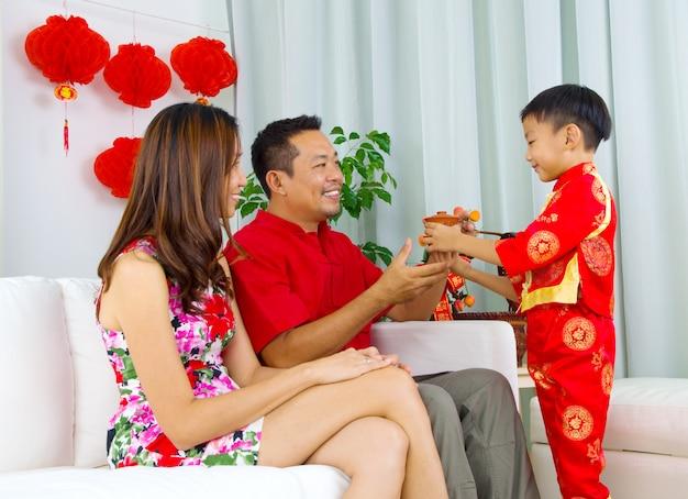 Aziatische jongen die thee voorstelt aan zijn vader tijdens chinees nieuw jaar