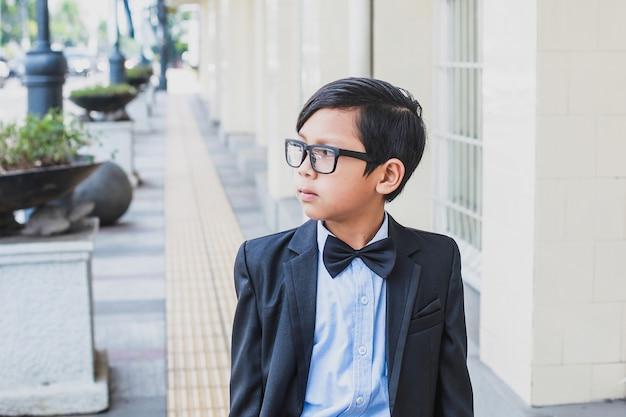 Aziatische jongen die vintage zwart pak en bril draagt die op de voetganger loopt terwijl hij op straat kijkt
