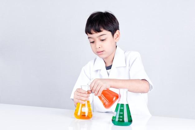 Aziatische jongen die wetenschapsexperiment met kleurenvloeistof doet