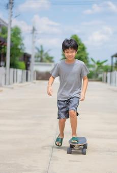 Aziatische jongen die zich op surfskate bevindt achtergrond van straten en huizen