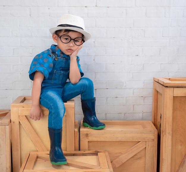 Aziatische jongen draagt blauwe kleding met laarzen.
