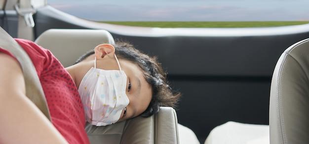 Aziatische jongen draagt een beschermend masker van coronavirus covid 19 epidermisch in de auto tijdens het reizen nieuw normaal