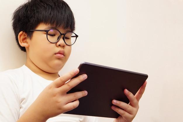 Aziatische jongen draagt een bril en speelt digitale tablet.