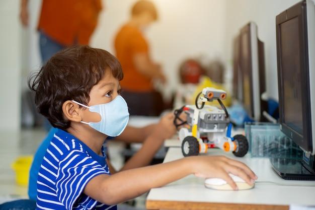 Aziatische jongen draagt gezichtsmaskers om het coronavirus 2019 (covid-19) op scholen te voorkomen.