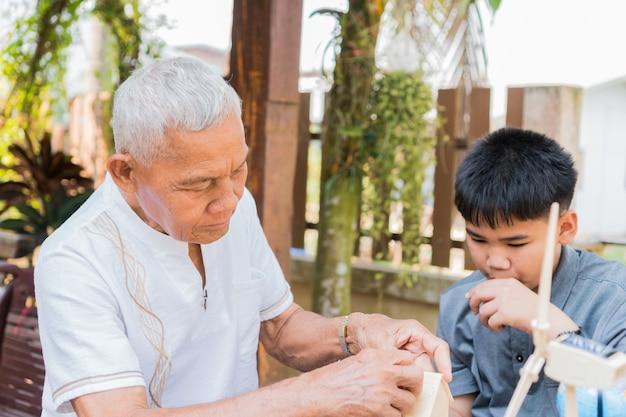 Aziatische jongen en gepensioneerde grootvader leren samen speelgoed huis bouwen of puzzel
