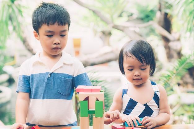 Aziatische jongen en gril spelen houten blok speelgoed op tafel.