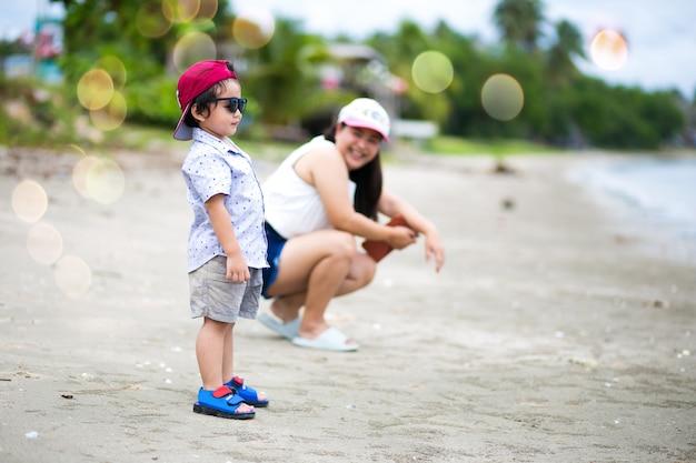 Aziatische jongen en moeder die het tropische strand lopen, gelukkige kleine jongen die dichtbij het overzees lopen