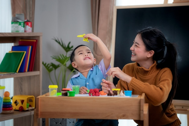 Aziatische jongen en zijn leraar spelen doh togather in de klas in de kleuterschool