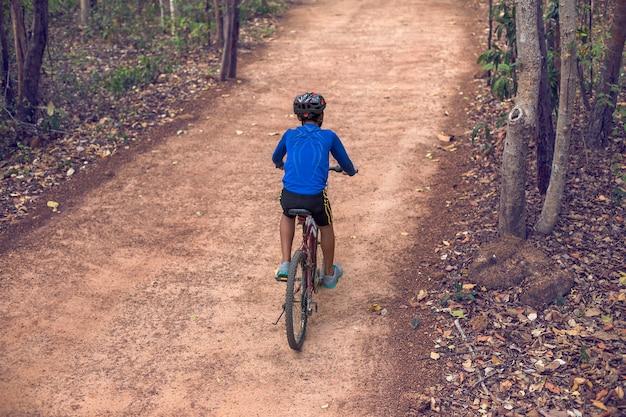 Aziatische jongen fietsen op landelijke wegen.