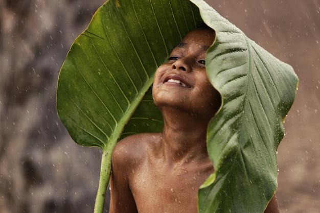 Aziatische jongen is blij omdat ze in de regen spelen. na een lange droogte