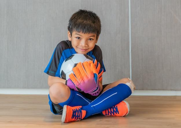 Aziatische jongen is een voetbalkeeper die handschoenen draagt en een voetbalbal met glimlachgezicht houdt.
