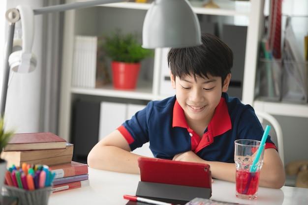 Aziatische jongen kijken op tablet pc