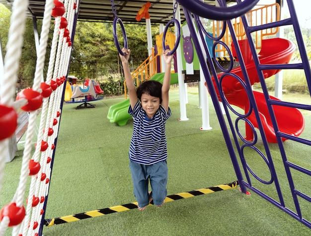 Aziatische jongen klimt op een speeltoestel in een school.
