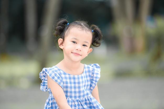 Aziatische jongen meisje gelukkig in de park tuin boom achtergrond, mooi kind plezier buiten spelen met een gelukkige glimlach kinderen buiten spelen meisje portret.