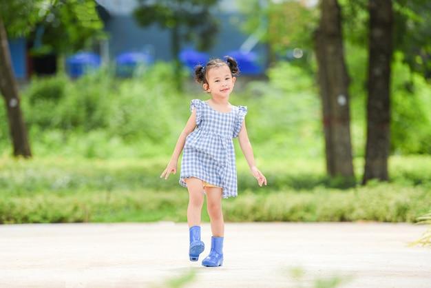 Aziatische jongen meisje gelukkig in de park tuin boom achtergrond, mooi kind plezier buiten spelen met gelukkige glimlach kinderen buiten spelen meisje portret dragen kleurrijke laarzen