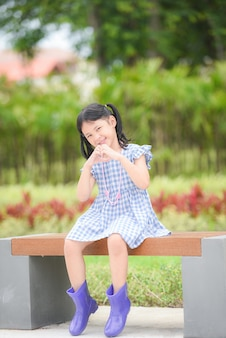 Aziatische jongen meisje gelukkig in de parktuin boom achtergrond, mooi kind plezier buiten spelen met gelukkige glimlach kinderen buiten spelen meisje portret dragen kleurrijke laarzen zitten bankje