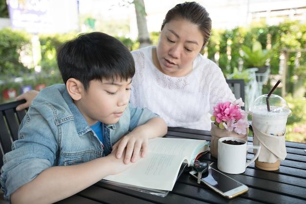 Aziatische jongen met moeder die en uw thuiswerk thuis onderwijzen leren