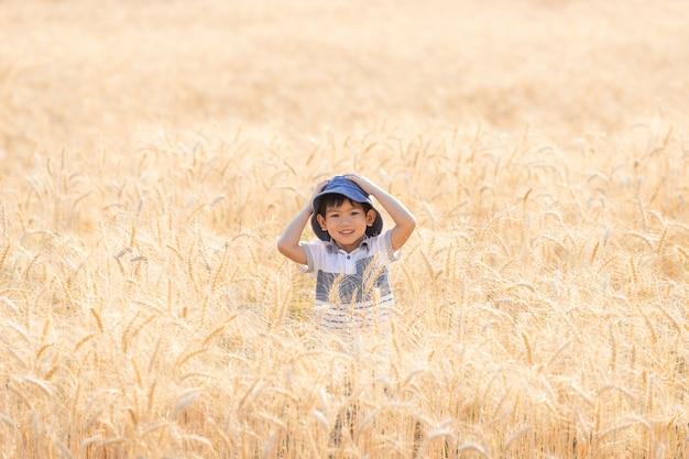 Aziatische jongen met plezier en spelen in een tarweveld op zomer.
