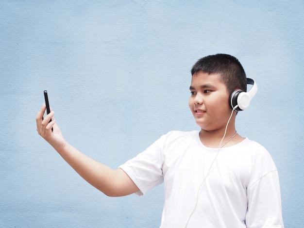 Aziatische jongen met wit overhemd die hoofdtelefoon dragen en mobiele telefoon over blauwe muurachtergrond spelen.