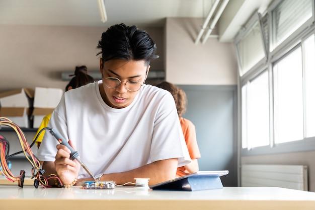 Aziatische jongen middelbare schoolstudent in de klas die elektronica leert met tablet kopieer de ruimte onderwijs