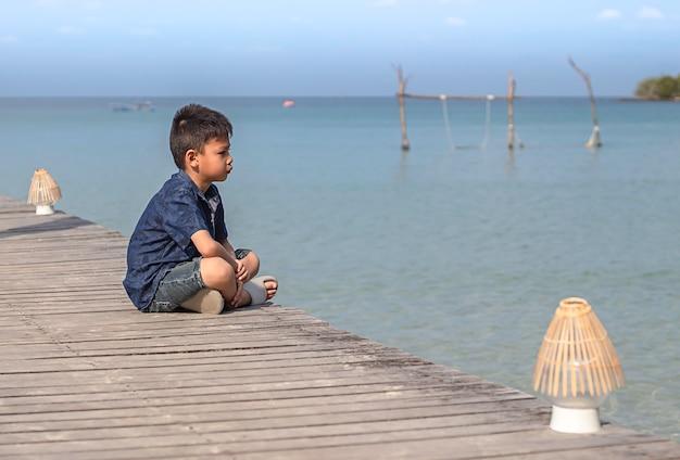 Aziatische jongen op de houten boot van de brugpijler in het overzees en de heldere hemel in koh kood, trat in thailand