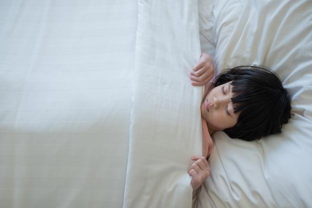 Aziatische jongen slapen op bed, ziek kind