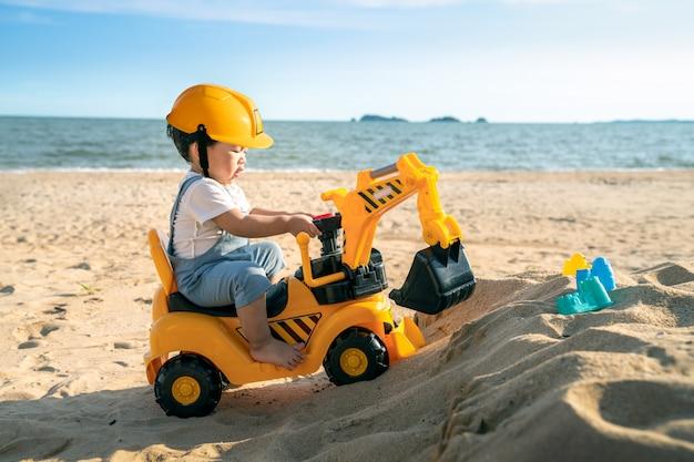 Aziatische jongen speelt een graafwerktuigstuk speelgoed op het strand
