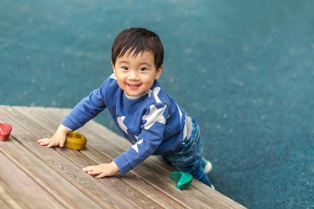 Aziatische jongen speelt in de speeltuin met een blij gezicht in de zomer. ruimte voor tekst kopiëren