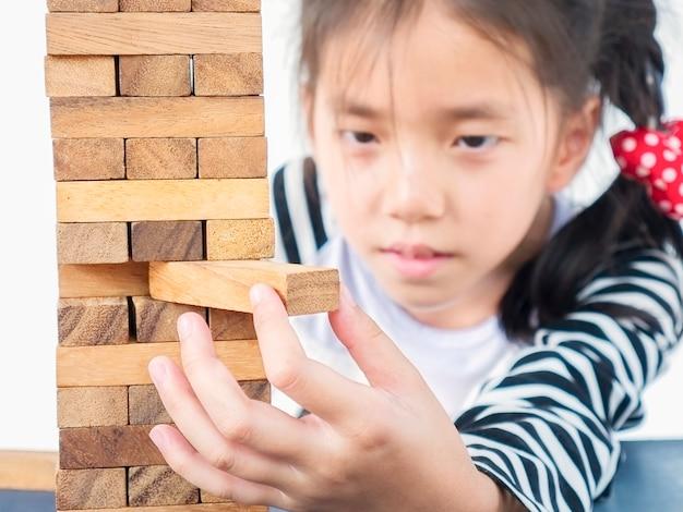 Aziatische jongen speelt jenga, een houten blokken torenspel voor het beoefenen van fysieke en mentale vaardigheden