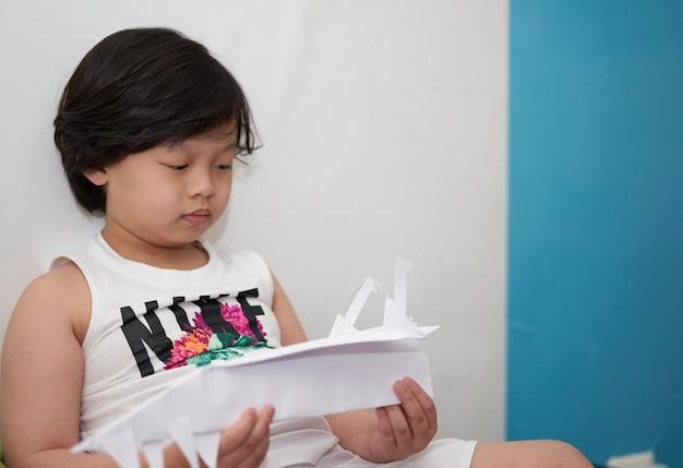 Aziatische jongen spelen papieren vliegtuig in de kamer
