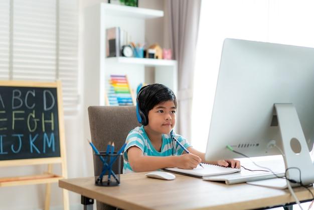 Aziatische jongen student videoconferentie e-learning met leraar en klasgenoten op de computer
