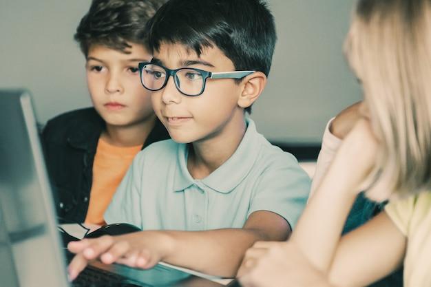 Aziatische jongen typen op laptop toetsenbord en klasgenoten aan tafel zitten, kijken naar hem en samen taak doen
